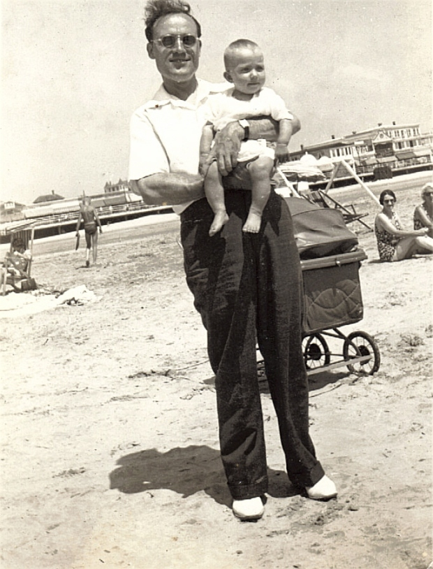 Man with Comb Over Holding a Baby at the Beach